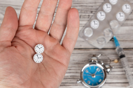 Time heals concept. Male hand holding pills stylized as clock.