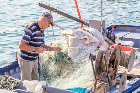 20 October 2014. Syracuse, Italy: Senior fisherman unraveling the net on the boat Stock fotó