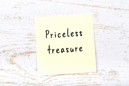 Yellow sticky note on wooden desk with handwritten text priceless treasure