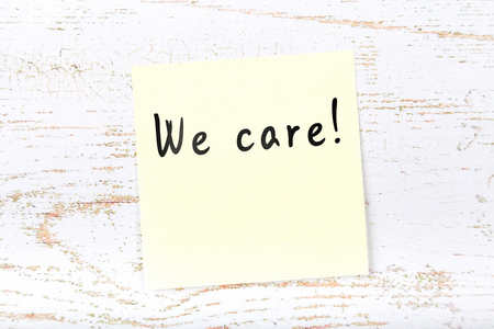 Yellow sticky note on wooden desk with handwritten text we care