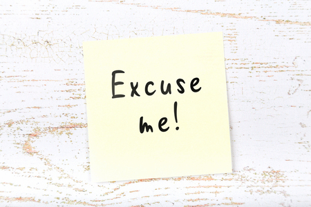Yellow sticky note on wooden desk with handwritten text excuse me Standard-Bild - 115332634