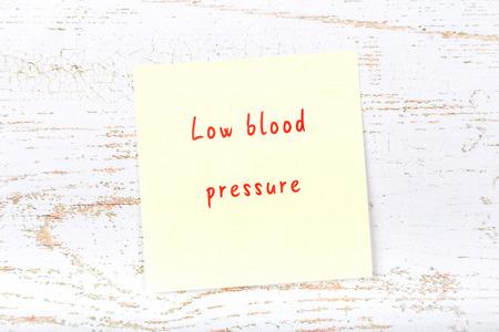Yellow sticky note on wooden desk with handwritten text high blood pressure Standard-Bild