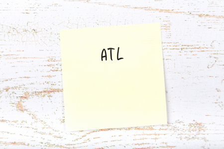 Yellow sticky note with handwritten text atl Stock Photo