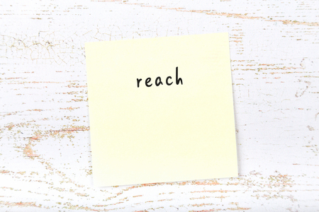 Yellow sticky note with handwritten text reach Imagens