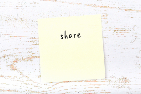 Yellow sticky note with handwritten text share Imagens