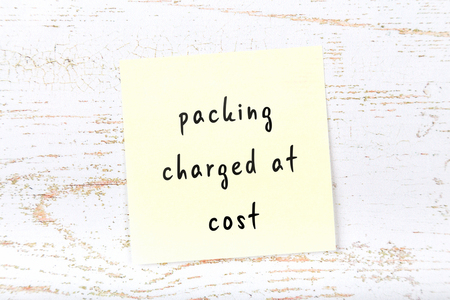 Yellow sticky note with handwritten text packing charged at cost Stock fotó - 116206547