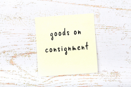 Yellow sticky note with handwritten text goods on consignment