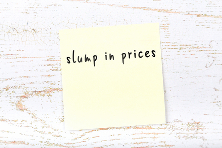 Yellow sticky note with handwritten text slump in prices