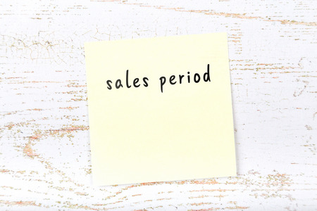 Yellow sticky note with handwritten text sales period Фото со стока