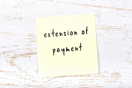 Yellow sticky note with handwritten text extension of payment Imagens