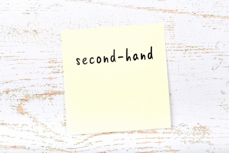 Yellow sticky note with handwritten text secondhand Stockfoto