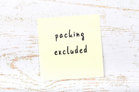 Yellow sticky note with handwritten text packing excluded Stock Photo