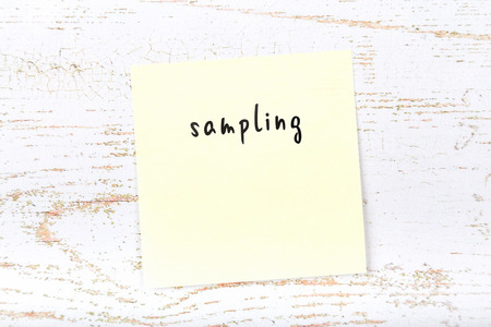 Yellow sticky note with handwritten text sampling Stok Fotoğraf