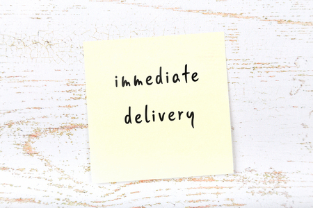 Yellow sticky note with handwritten text immediate delivery