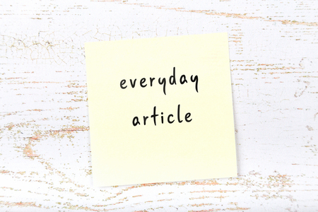 Yellow sticky note with handwritten text everyday article Imagens