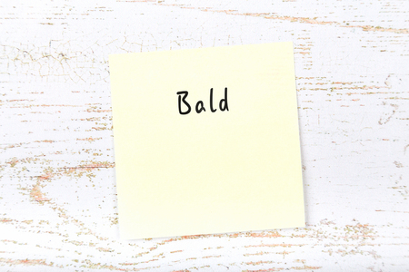 Yellow sticky note with handwritten word bald