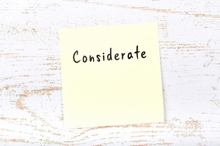 Yellow sticky note with handwritten word considerate Stok Fotoğraf