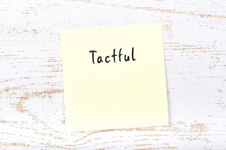 Yellow sticky note with handwritten word tactful 版權商用圖片