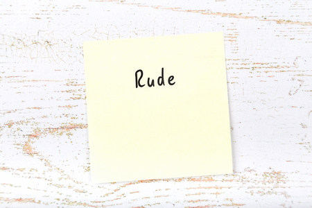 Yellow sticky note with handwritten word rude