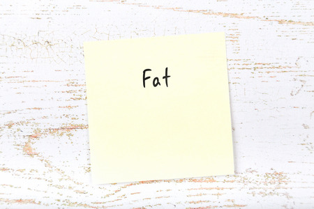 Yellow sticky note with handwritten word fat 版權商用圖片