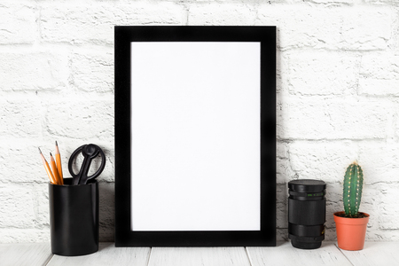 Empty black photo frame on wooden shelf or table. Mockup with copy space