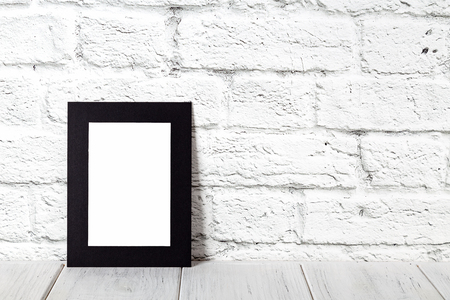 Vertical black photo frame on wooden table. Mockup with copy space. Foto de archivo