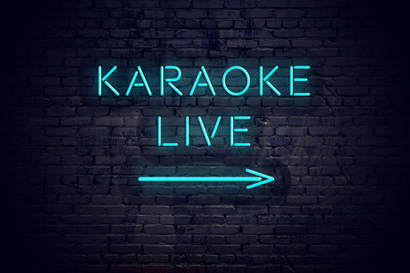 Brick wall with neon arrow and sign karaoke live