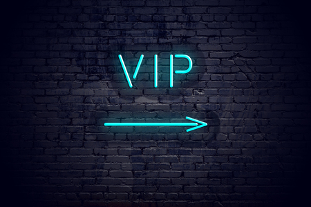 Brick wall with neon arrow and sign vip