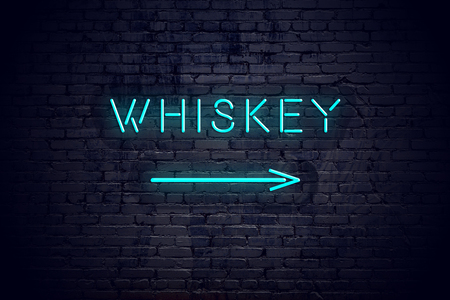Brick wall with neon arrow and sign whiskey Imagens