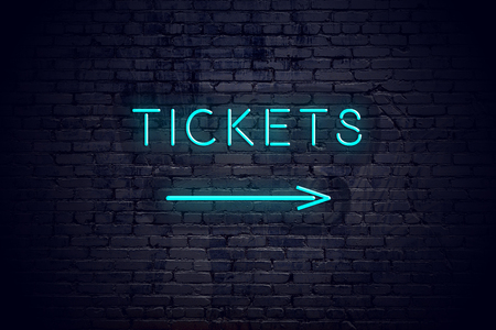 Brick wall with neon arrow and sign tickets