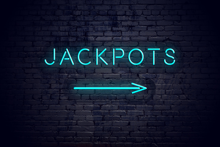 Brick wall with neon arrow and sign jackpots
