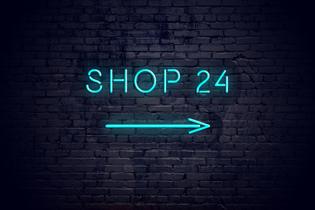 Brick wall with neon arrow and sign shop 24