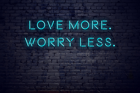 Neon sign with short motivational quote against brick wall. Stock Photo