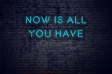 Neon sign with short motivational quote against brick wall.