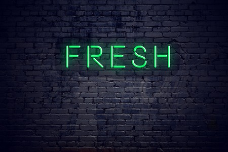 Brick wall at night with neon sign fresh.