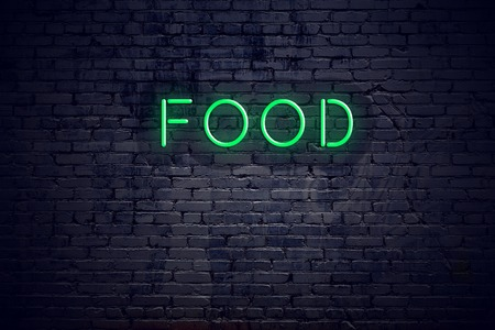 Brick wall at night with neon sign food.