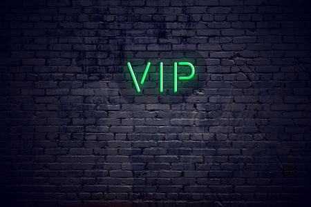 Brick wall at night with neon sign vip. Reklamní fotografie