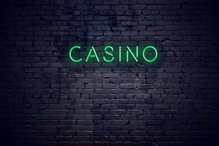Brick wall at night with neon sign casino.