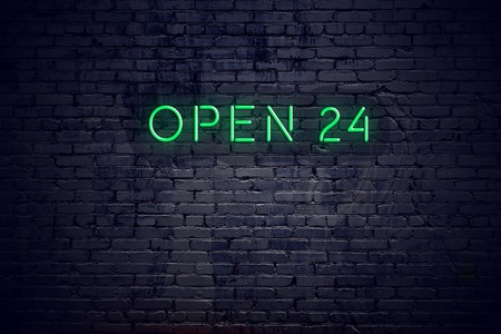 Brick wall at night with neon sign open 24.