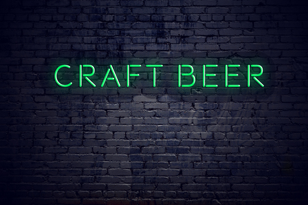 Brick wall at night with neon sign craft beer.