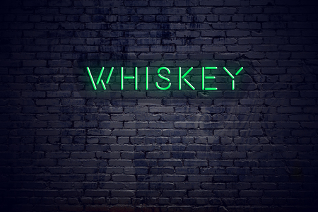 Brick wall at night with neon sign whiskey.