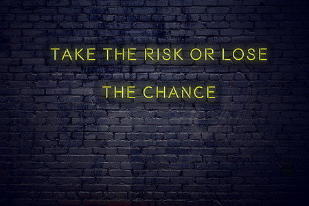 Positive inspiring quote on neon sign against brick wall take the risk or lose the chance.