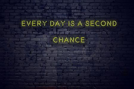 Une citation inspirante positive sur une enseigne au néon contre un mur de briques est chaque jour une seconde chance. Banque d'images