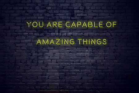Positive inspiring quote on neon sign against brick wall you are capable of amazing things.