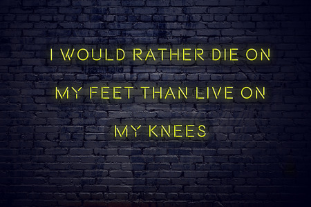 Positive inspiring quote on neon sign against brick wall i would rather die on my feet than live on my knees.