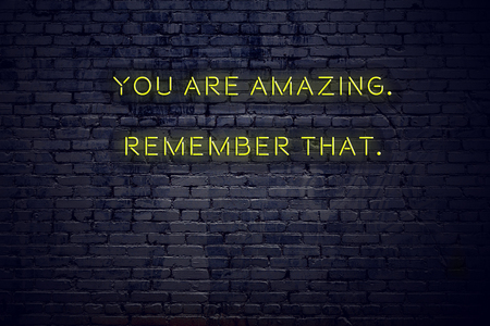 Positive inspiring quote on neon sign against brick wall you are amazing remember that. 写真素材