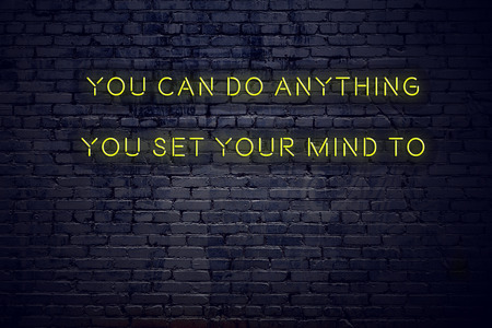 Positive inspiring quote on neon sign against brick wall you can do anything you set your mind to.