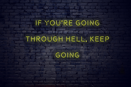 Positive inspiring quote on neon sign against brick wall if youre going through hell keep going.