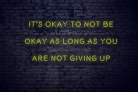 Positive inspiring quote on neon sign against brick wall its okay to not be okay as long as you are not giving up. Stock fotó
