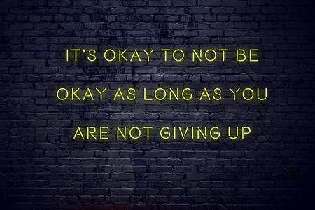 Pozytywny inspirujący cytat na neonowym znaku na ceglanej ścianie jest w porządku, aby nie być w porządku, o ile się nie poddajesz.